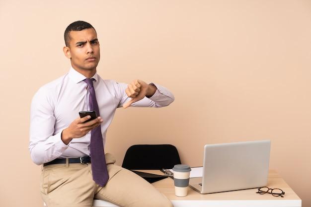 Homme d'affaires jeune dans un bureau montrant le signe du pouce vers le bas