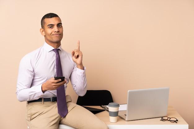 Homme d'affaires jeune dans un bureau pointant avec l'index une excellente idée
