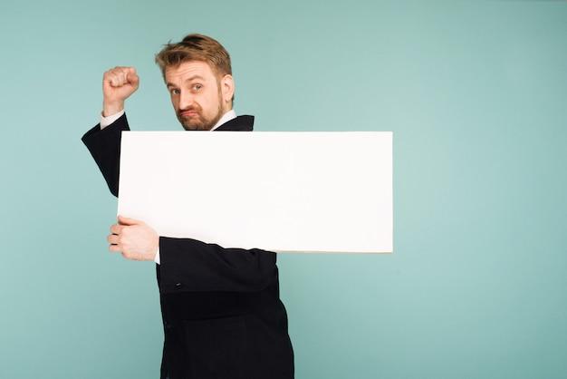 Homme d'affaires jeune drôle montrant une pancarte vierge, sur bleu
