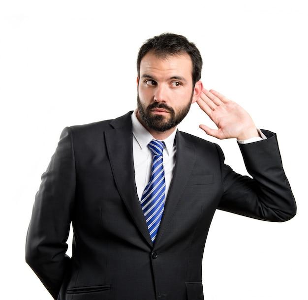 Homme d'affaires jeune entendre quelque chose sur fond blanc