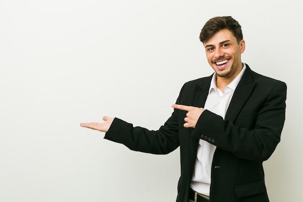Homme d'affaires jeune excité tenant quelque chose
