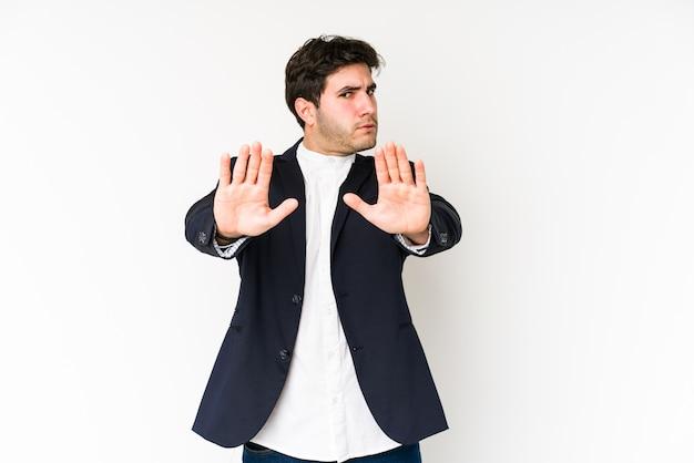 Homme d'affaires jeune isolé sur blanc debout avec la main tendue montrant le panneau d'arrêt, vous empêchant.