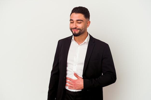 Homme d'affaires jeune métisse isolé sur fond blanc touche le ventre, sourit doucement, concept de manger et de satisfaction.