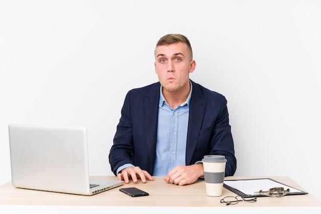 Homme d'affaires jeune avec un ordinateur portable hausse les épaules et les yeux ouverts confus.