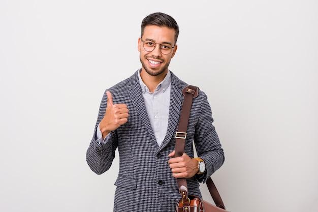 Homme d'affaires jeune philippin contre un mur blanc souriant et levant le pouce vers le haut