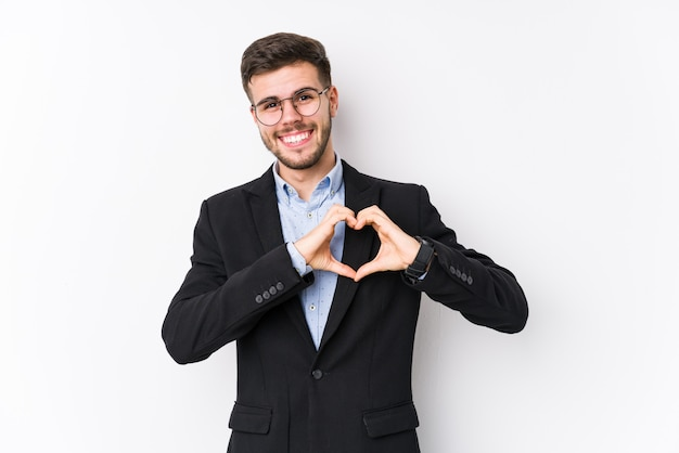 Homme d'affaires jeune posant homme d'affaires jeune souriant et montrant une forme de coeur avec les mains