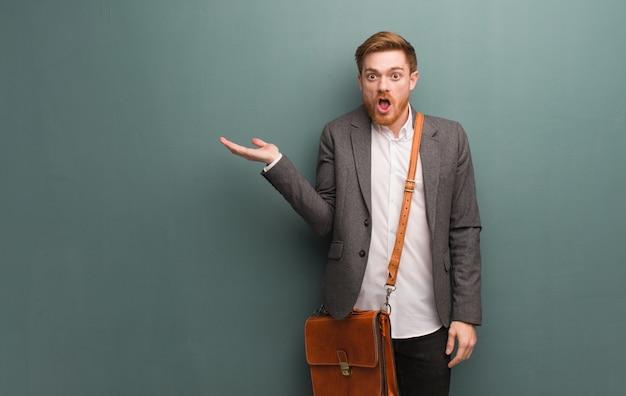 Homme d'affaires jeune rousse tenant quelque chose sur la main de paume