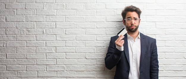 Homme d'affaires jeune vêtu d'un costume contre un mur de briques blanches inquiet et accablé