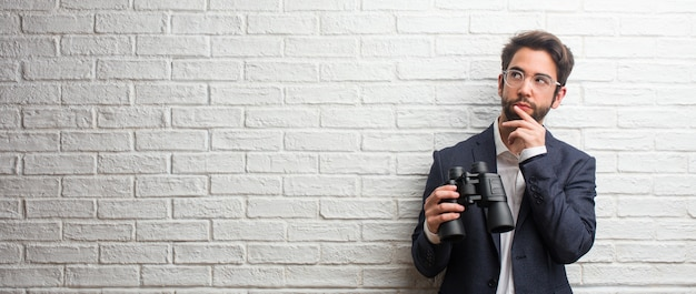 Homme d'affaires jeune vêtu d'un costume contre un mur de briques blanches pensant et levant