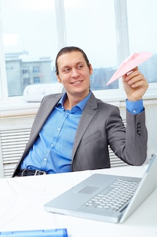 Homme d'affaires en jouant avec un avion de papier