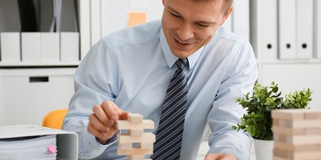 Homme d'affaires joue dans une stratégie de main jenga