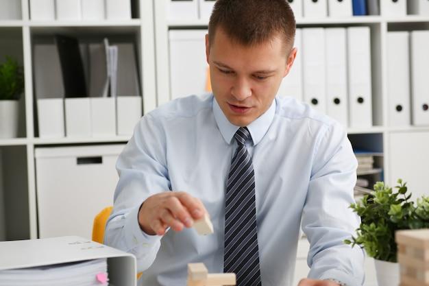 Homme d'affaires joue dans la stratégie à la main en réorganisant les blocs de bois impliqués pendant la pause au travail dans le bureau assis table de jeu pile fun joie passe-temps concept