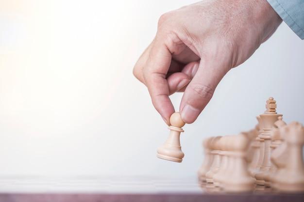 Homme d'affaires joue avec le jeu d'échecs dans le succès de la compétition