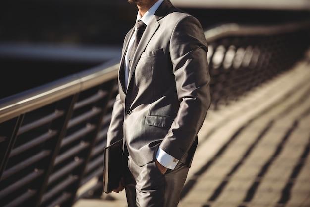 Homme affaires, journal, debout, bureau, terrasse