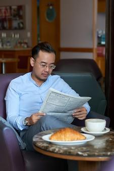 Homme affaires, journal lisant, dans, coffeshop