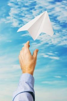 Homme d'affaires a lancé un avion en papier dans le ciel comme symbole d'une nouvelle entreprise