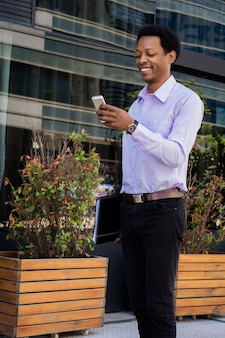 Homme d'affaires latin à l'aide de téléphone portable dans la ville