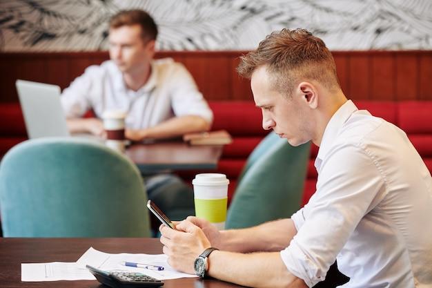 Homme d'affaires, lecture de nouvelles sur l'écran du smartphone