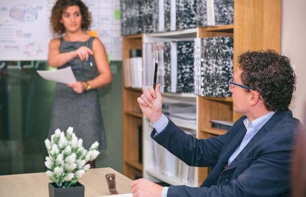 Homme d'affaires levant un crayon à la main tout en ayant une question à l'entraîneur féminin après une réunion d'affaires au siège