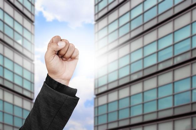 Homme d'affaires levant les poings en l'air avec le bâtiment flou.