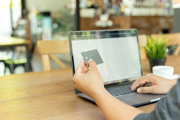 Homme d'affaires en ligne travaillant main tenant la carte de crédit et à l'aide d'ordinateur portable au café.