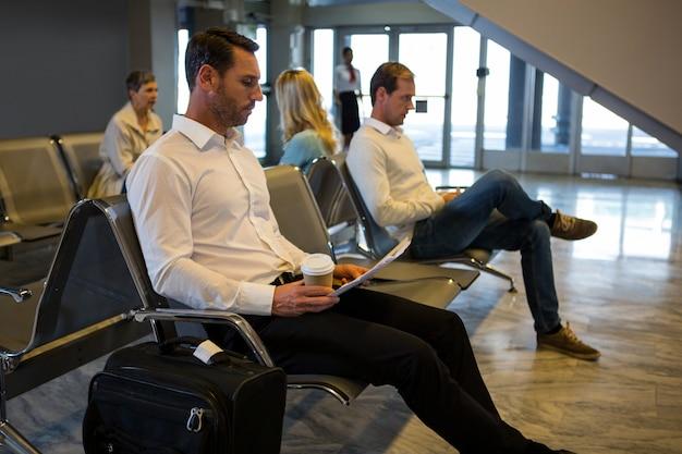 Homme d'affaires lisant le journal dans la zone d'attente