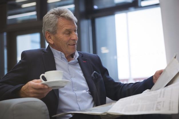 Homme d'affaires lisant le journal tout en prenant un café