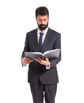 Homme d'affaires lisant un livre sur fond blanc