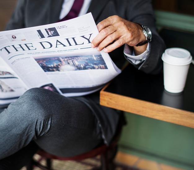 Homme d'affaires lisant les nouvelles quotidiennes