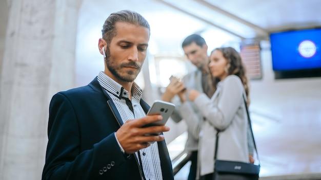 Homme d'affaires lisant un sms en se tenant debout dans les escaliers dans le métro