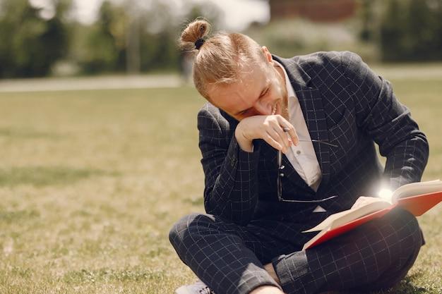 Homme d'affaires avec livre assis dans une ville d'été