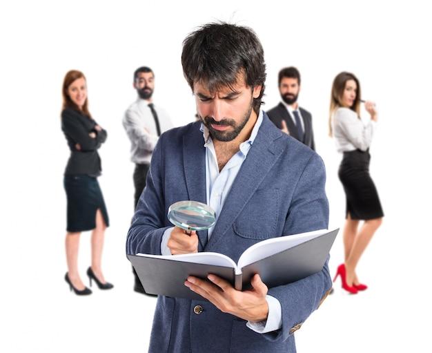 Homme d'affaires avec loupe reding un livre sur fond blanc