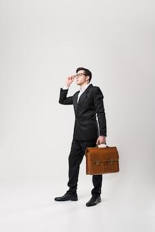 Homme d'affaires à lunettes et costume noir tient une mallette en cuir marron à la main isolé sur blanc