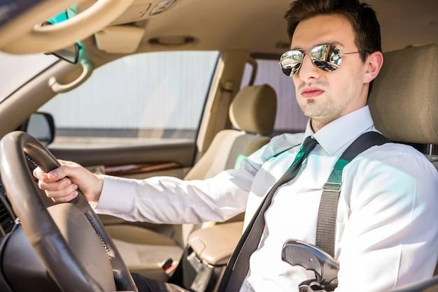 Homme d'affaires en lunettes de soleil avec arme à feu dans sa voiture de luxe.