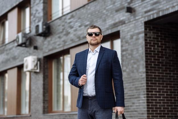 Homme d'affaires à lunettes de soleil et un costume avec un sac sur les lieux d'une rue de la ville