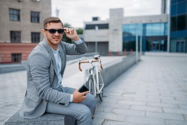 Un homme d'affaires en lunettes de soleil pose à vélo dans l'immeuble de bureaux au centre-ville. homme d'affaires à cheval sur le transport écologique sur la rue de la ville