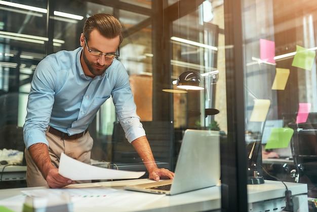 Homme d'affaires à lunettes et vêtements de cérémonie examinant des documents en se tenant debout dans le bureau moderne