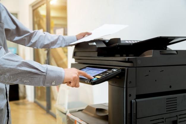 Homme d'affaires main appuyez sur le bouton sur le panneau de l'imprimante, imprimante scanner laser bureau copie machine fournitures commencent