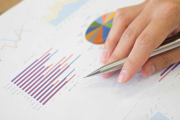 Homme d'affaires main avec un stylo écrit sur les documents statistiques