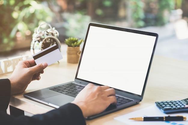 Homme d'affaires main tenant la carte de crédit et à l'aide d'ordinateur portable sur le bureau avec document et calculatrice.