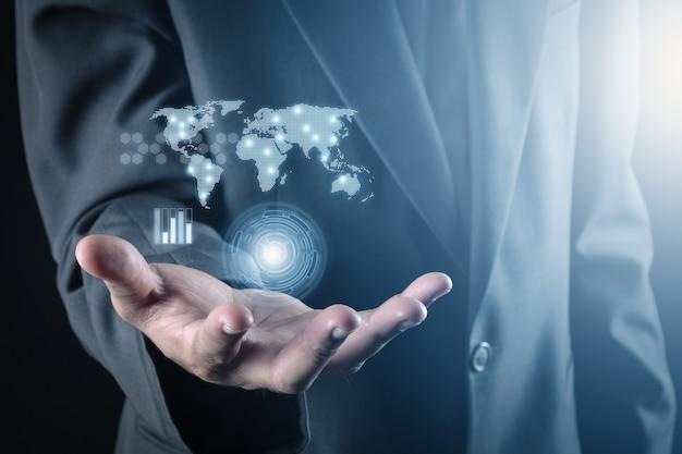 Homme d'affaires et main tenant la carte du monde du réseau de données et d'information