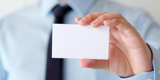 Homme d'affaires main tenant une carte de visite blanche vierge avec espace de copie pour le texte