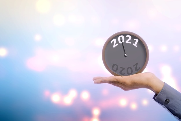Homme d'affaires main tenant horloge en attente de 2021. bonne année 2021