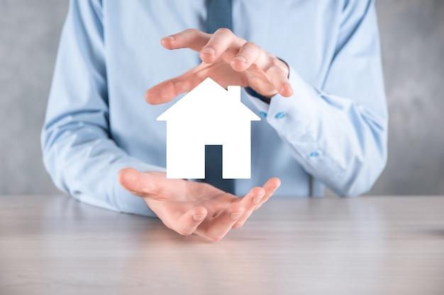 Homme d'affaires main tenant l'icône de la maison sur fond bleu. concept d'assurance et de sécurité des biens. concept immobilier. bannière avec espace de copie.