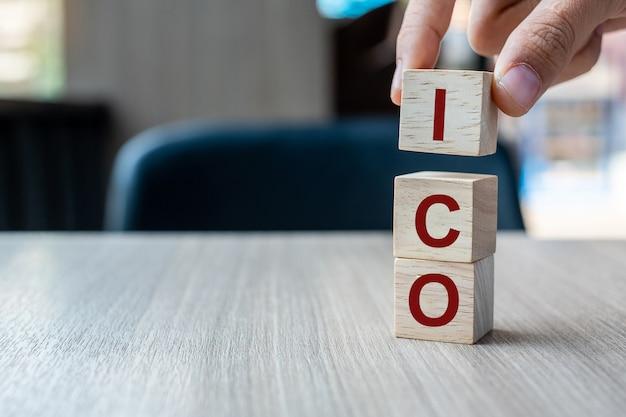 Homme d'affaires main tenant le mot ico (offre initiale de pièces) avec un bloc de cube en bois