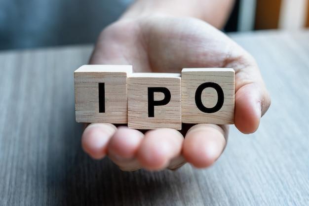 Homme d'affaires main tenant le mot ipo (offre publique initiale) avec bloc de cube en bois