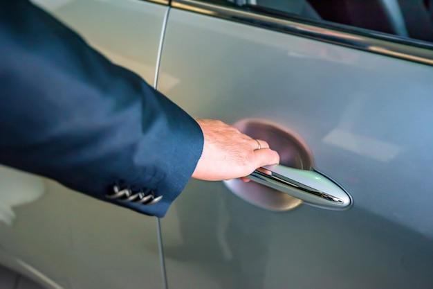 Homme d'affaires main tenant la poignée de voiture