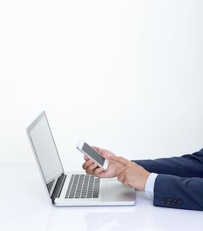 Homme d'affaires main tenant le smartphone avec ordinateur portable