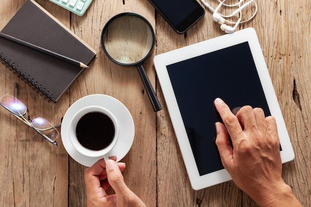 Homme d'affaires à la main tenant une tasse de café blanc avec tablette à utiliser sur le bureau en bois et les objets de l'entreprise.