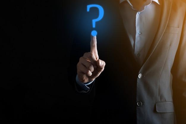 Homme d'affaires main tenir interface points d'interrogation signe web. posez des questions en ligne, un concept de faq, quoi où quand comment et pourquoi, recherchez des informations sur internet.